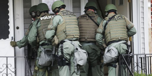 SWAT members approach a home during the search for suspects of the Boston Marathon bombings.