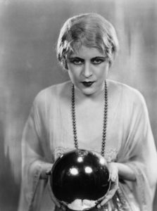17th April 1928: Ruby Miller holding a crystal ball in a scene from the play 'The Monster' at the Strand Theatre, London. (Photo by Sasha/Getty Images)
